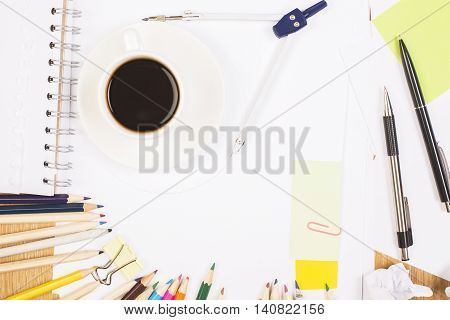 Top view of office workplace with colorful pencils coffee cup notepad pair of compasses and other stationery items