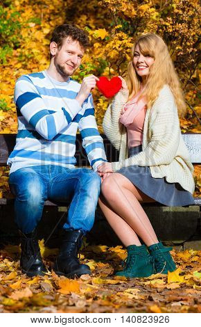 Romantic Pair Sit On Bench In Autumnal Park