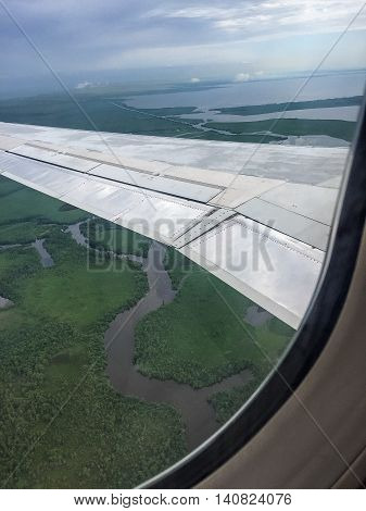 Plane wing over swamp water. Pretty aerial view.