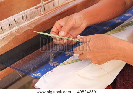 Close up of woman hand weaving traditional silk farbric on loom