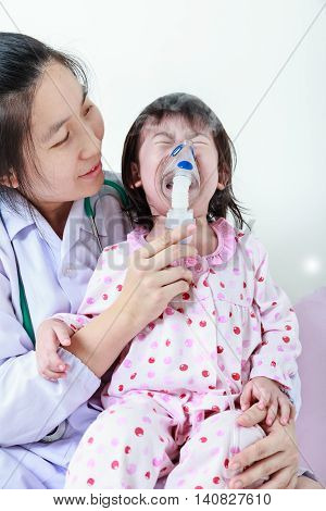 Sad child having respiratory illness helped by health professional with inhaler. Pediatrician take care asian girl with asthma problems making inhalation with mask on her face at hospital. Child crying.