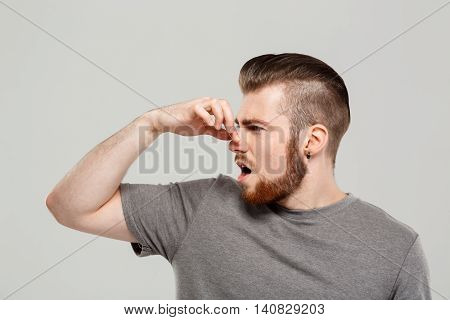 Young handsome man pinching nose from smell over grey background. Copy space.