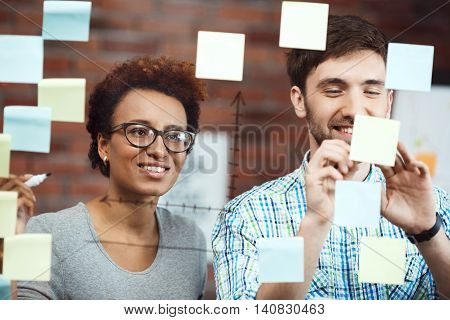 Colleagues making business plan, smiling, speaking at meeting