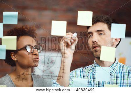 Colleagues making business plan, smiling, speaking at meeting
