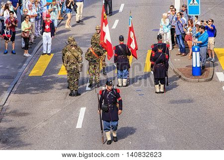 Zurich, Switzerland - 1 August, 2016: participants of the parade devoted to the Swiss National Day on Uraniastrasse street. The Swiss National Day is the national holiday of Switzerland, set on 1 August.