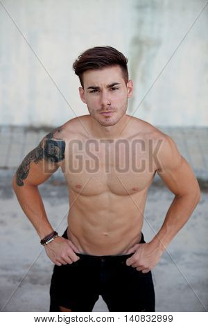 Handsome fit athletic shirtless young man with a tattoo