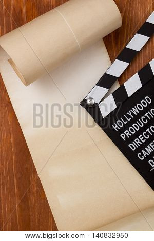 Clapper for film and paper roll on the wooden background