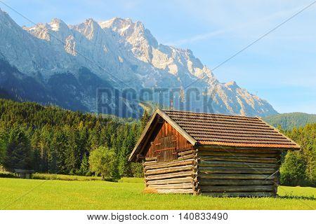 Hayloft in alpine landscape under Zugspitze. It is Germany's highest peak (2962 m). View from a Garmisch Partenkirchen valey. European destinations for hiking, skiing and mountaineering.