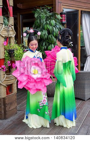 Beautiful Chinese Women In Green Traditional Dresses And Floral Parasol