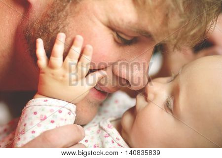 A happy father is playing with his newborn baby daughter lovingly touching noses while she puts her hand on his cheek. Shallow depth of field.