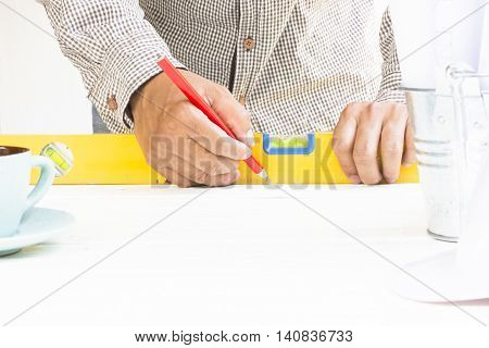Carpenter working with level equipment and wood pencil in his  hand on white table.
