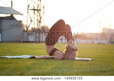 Young blonde woman in sportswear practicing yoga in park. Scorpion Pose Chest Stand Head to Foot.