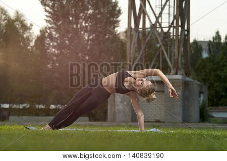 Slim blonde woman doing yoga on green grass. Side Plank Pose