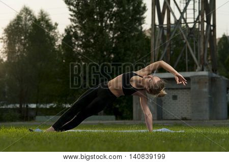 Yoga outdoors: fit woman in black sportswear practicing outdoors. Side Plank Pose.