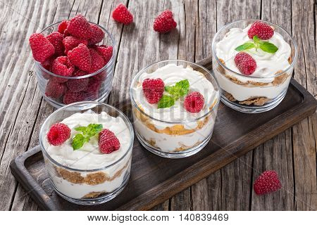 homemade yogurt in cups with whole grain cereals and corn flakes and raspberry decorated with mint leaves on wooden table view from above