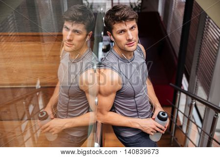 Young handsome sports man holding bottle with water and resting in the gym with earphones