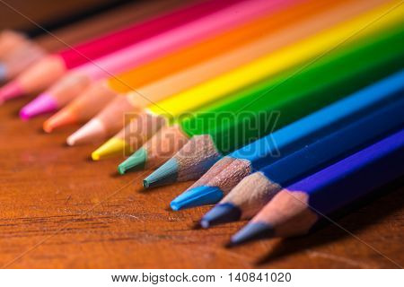 A row of colorful coloring pencils displayed on a wooden background