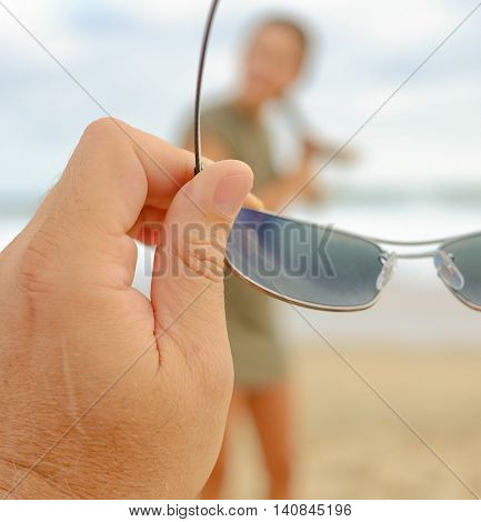 Man's hand holding a pair of glasses with a woman in the background.