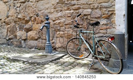 A vintage bicycle parked next to a cast iron well pump.