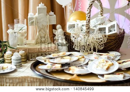 Cake on small plates sitting atop a child's baptismal gift table.