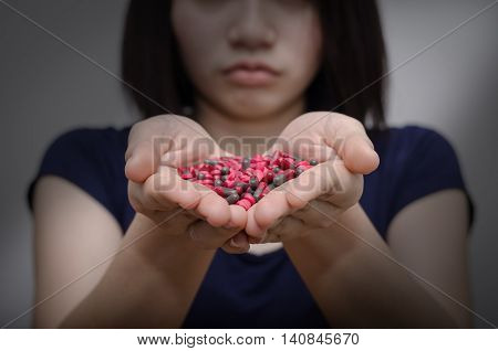 Unhappy asian girl with many medicine pills on hand