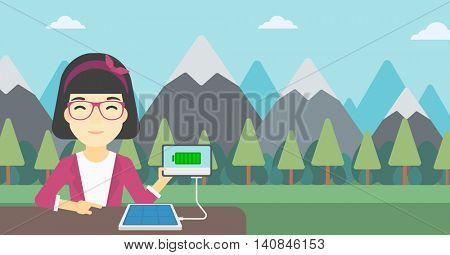 An asian woman charging tablet computer with solar panel on a background of mountains. Charging digital tablet from portable solar panel. Vector flat design illustration. Horizontal layout.