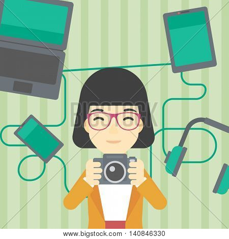 An asian young woman taking photo with digital camera. Woman surrounded with her electronic gadgets. Woman using many electronic gadgets. Vector flat design illustration. Square layout.