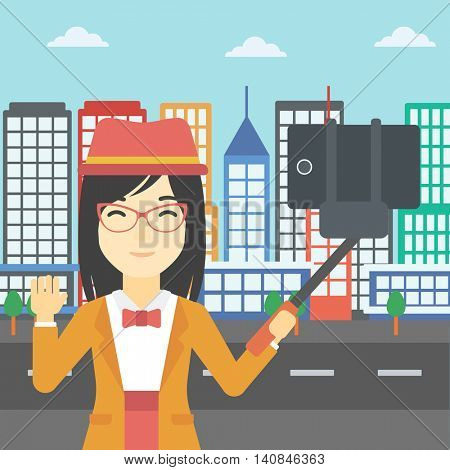 An asian woman making selfie with a selfie-stick. An asian woman taking photo with cellphone and waving on a city background. Vector flat design illustration. Square layout.