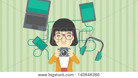 An asian young woman taking photo with digital camera. Woman surrounded with her electronic gadgets. Woman using many electronic gadgets. Vector flat design illustration. Horizontal layout.