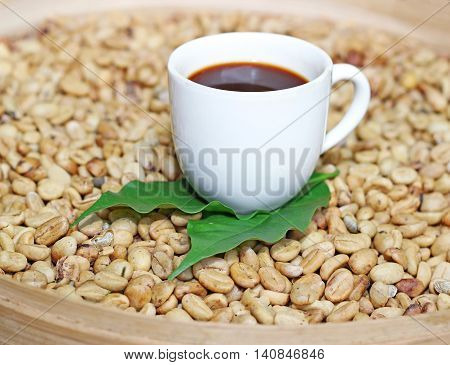 luwak beans and white cup of coffee in a basket