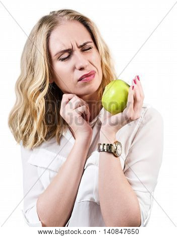Woman with green apple feels toothpain because of sensitive gums isolated on white
