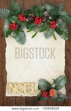 Christmas abstract background border with gold glitter noel sign, robin decoration, holly, ivy, mistletoe and snow covered fir on parchment paper over oak.