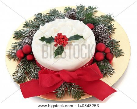Christmas cake with icing sugar and holly berries, snow covered winter greenery, red baubles and ribbon with bow on a gold plate over white background.