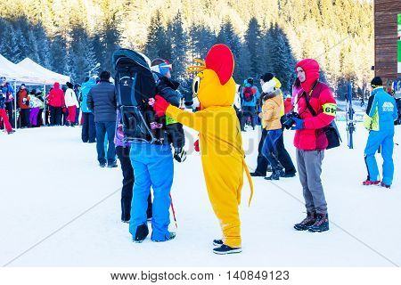 Bansko, Bulgaria - December 12, 2015: People taking photos with mouse in costume at ski resort
