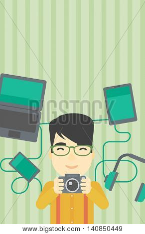 An asian young man taking photo with digital camera. Man surrounded with gadgets. Man using many electronic gadgets. Vector flat design illustration. Vertical layout.