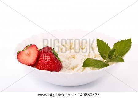 Natural cottage cheese with fresh ripe strawberries and leaf of mint on a white background