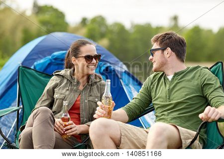 camping, travel, tourism, hike and people concept - happy couple drinking beer or cider at campsite tent