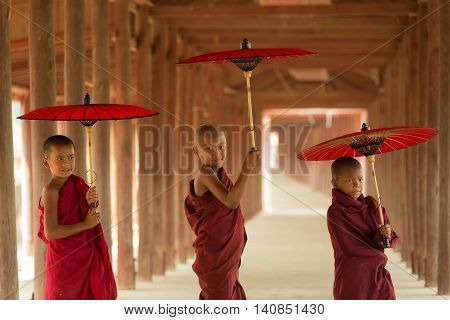 Three Novice monks standing holding red umbrella