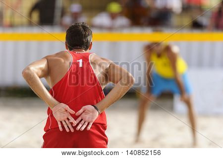 Volleyball player is a male volleyball player giving signals to his partner as his opponent waits for the serve.