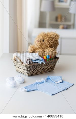 babyhood, motherhood, clothing and object concept - close up of baby clothes and toys for newborn boy in basket at home
