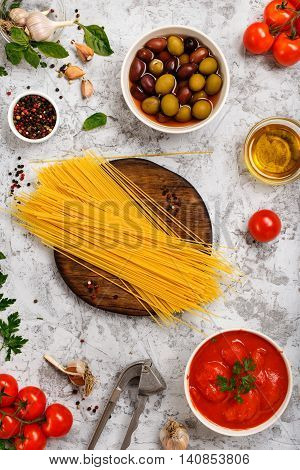 Italian spaghetti with olives peppers olive oil garlic basil parsley and tomatoes on rude light surface top view. Italian food ingredients background