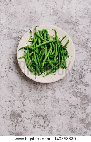 French bean in white plate on the light surface top view