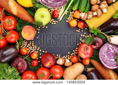 Frame of colorful different fruits vegetables pasta chickpea and bread on dark surface. Frame of colorful different food top view