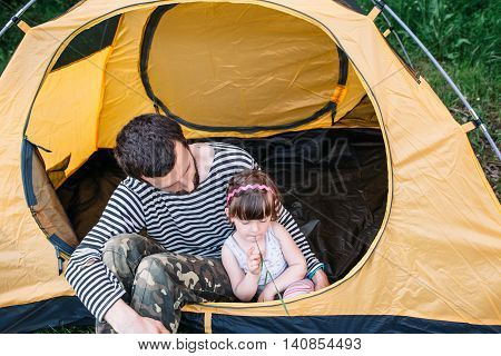 Dad with his little daughter in tent on camping. Interesting family journey, travel photo