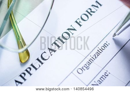 Close up of a job application form on desk with pen and glasses