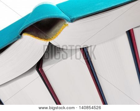 Book stack with open book, studio shot.
