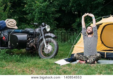 Happy man relaxing in forest on summer morning. Long-awaited trip to nature, motorcycle with sidecar journey alone