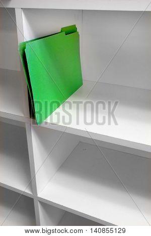 Single Green file on shelf for information storage
