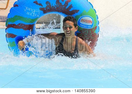 Rhodes Greece-July 15,2016:Young girl in the pool after mat racer slide.Mat racer slide is very popular for young people in the Water Park.Water Park is located on the island of Rhodes in Greece and one of the most largest in Europe