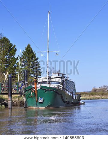 Anchored sailboat at a pier. River with anchored sailing ship. Water reflections and blue sky on a sunny day in the wetland.